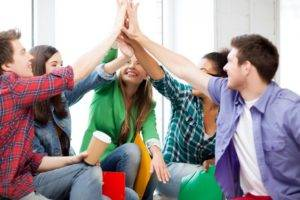 education concept - students giving high five at school